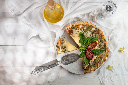 French opened pie quiche with tuna  chicken, broccoli, spinach, pepper, eggs, cheese and dried tomato on white wooden background. Copy space. Top view.