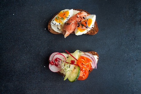 Healthy breakfast toasts. Wholegrain rye bread slice with cream cheese, eggs, salmon, sesam and microgreen. Clean eating concept. Yellow background. Top view. Copy space.
