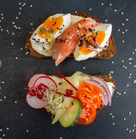 Healthy breakfast toasts. Wholegrain rye bread slices with cream cheese, eggs, salmon, carrot, cucumber, radish, sesam and microgreen. Clean eating concept.