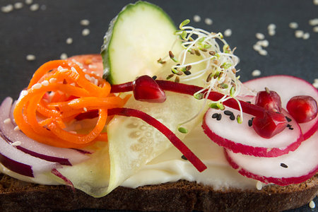 Healthy breakfast toast. Wholegrain rye bread slice with cream cheese, carrot, cucumber, radish, sesam and microgreen. Clean eating concept. Close up.