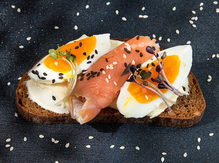 Healthy breakfast toasts. Wholegrain rye bread slices with cream cheese, eggs, salmon, sesam and microgreen. Clean eating concept. Copy space. Top view. Stok Fotoğraf