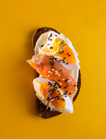 Healthy breakfast toasts. Wholegrain rye bread slices with cream cheese, eggs, salmon, sesam and microgreen. Clean eating concept. Yellow background. Top view.