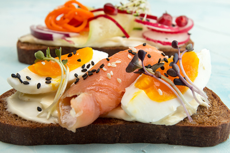 Healthy breakfast toasts. Wholegrain rye bread slices with cream cheese, eggs, salmon, sesam and microgreen. Clean eating concept.