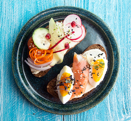 Healthy breakfast toasts. Wholegrain rye bread slices with cream cheese, eggs, salmon, carrot, cucumber, radish, sesam and microgreen. Clean eating concept. Top view. Stock Photo