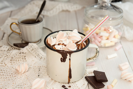 Mug of hot chocolate drink with marshmallow candies on top and candles on white background. Stock Photo