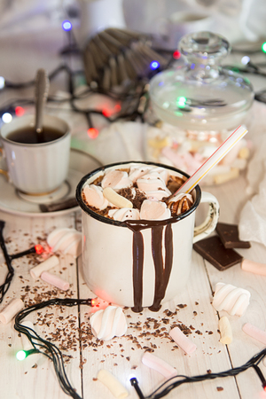 Mug of hot chocolate drink with marshmallow candies on top and candles on white background. Stockfoto