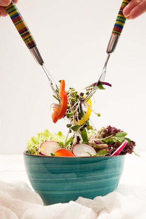 Blue bowl with fresh vegetarian salad of raw vegetables and microgreen on white background. Two forks. Salad ready-to-eat. Stockfoto