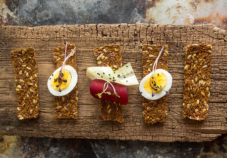Row of raw bread with sunflower seeds, carrots, sesame, flax seed and other vegetables. Egg halves, microgreen, cucumber and beetroot slices on old wooden background. Healthy eating concept.