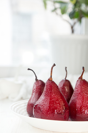 Pears in wine. Traditional dessert pears stewed in red wine with wine sauce on plate on white background. Concept for romantic dinner dessert.