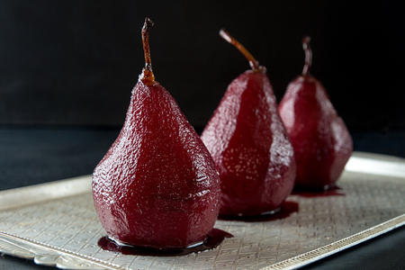 Pears in wine. Row of raditional dessert pears stewed in red wine on black background. Copy space