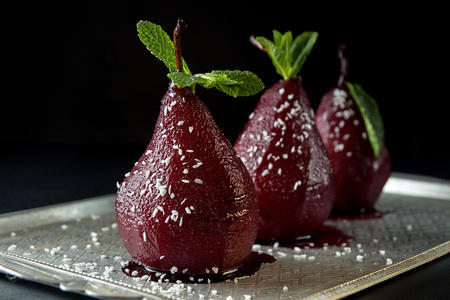 Pears in wine. Row of raditional dessert pears stewed in red wine on black background. Stockfoto