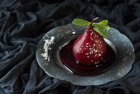 Pears in wine. Traditional dessert pears stewed in red wine on black fabric background. Copy space Stockfoto