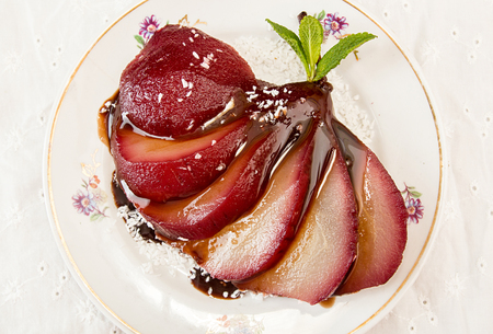 Pears in wine. Traditional dessert pears stewed in red wine with chocolate sauce on plate on white background. Top view