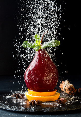 Pears in wine. Traditional dessert pears stewed in red wine on black background. Sugar powder strewing above.