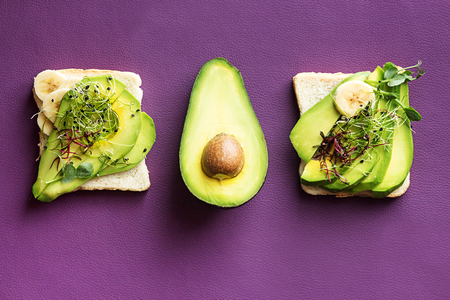 Healthy breakfast toasts with cream cheese, slices of avocado, banana and microgreen. Clean eating vegan dieting concept. Trend color ultraviolet background. Top view. Copy space.