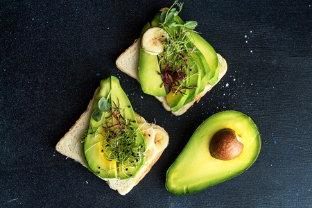Healthy breakfast toasts with cream cheese, slices of avocado, banana and microgreen on dark background. Clean eating vegan dieting concept. Top view. Copy space.