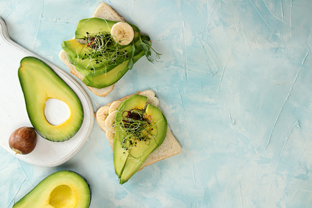 Healthy breakfast toasts with cream cheese, slices of avocado, banana and microgreen on blue background. Clean eating vegan dieting concept. Top view. Copy space. Stockfoto