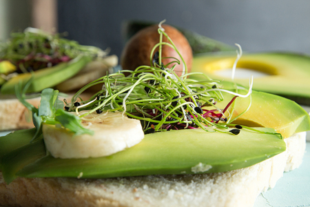 Healthy breakfast toasts with cream cheese, slices of avocado, banana and microgreen on concrete background. Clean eating vegan dieting concept. Close up.