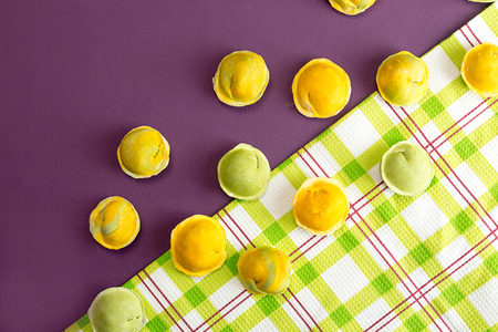 Row of homemade raw dumpling green and yellow colors, traditional East European food before boiling. Trend ultraviolet color background. Top view. Copy space. Stockfoto