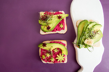 Healthy breakfast toast with feta, beetroot, slices of avocado and microgreen. Clean eating vegan dieting concept. Trend color ultraviolet background. Top view. Copy space.