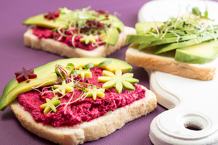 Healthy breakfast toasts with feta, beetroot, slices of avocado and microgreen. Clean eating vegan dieting concept. Trend color ultraviolet background. Top view. Copy space. Stockfoto