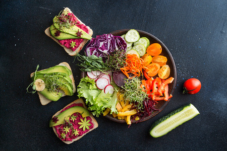 Healthy breakfast salad and toasts with vegetables and microgreen on dark background. Clean eating vegeterian dieting healthy food concept. Top view. Copy space.