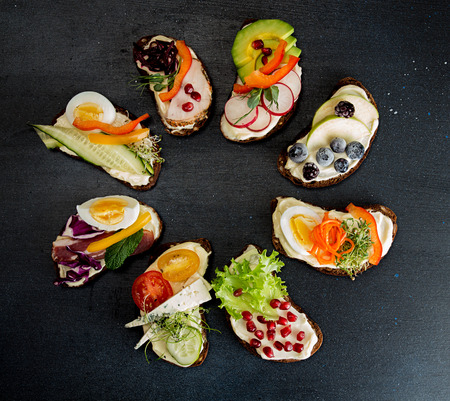 Healthy breakfast toasts with vegetables, fruits , meat and microgreen on dark background. Clean eating healthy food concept. Top view. Copy space.