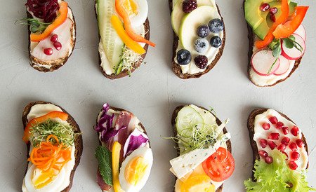Healthy breakfast toasts with vegetables, fruits , meat and microgreen on concrete background. Clean eating healthy food concept. Top view.