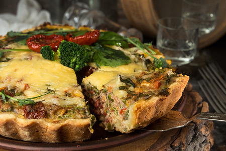 French opened pie quiche with tuna  chicken, broccoli, spinach, pepper, eggs, cheese and dried tomato on rustic background. Stockfoto