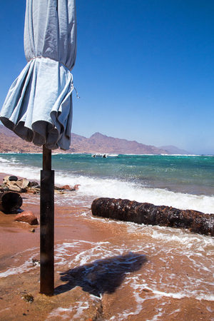 Closed sunchade at beach. Seascape Red Sea, Dahab, Sinai, Egypt. Stockfoto
