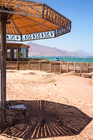 Sunshade on the beach, shade on sandd. Coastline of The Red Sea in Dahab, Egypt. Stockfoto