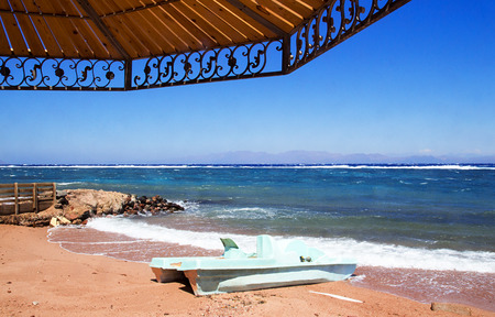 Sunshade on the beach, shade on sand. Coastline of The Red Sea in Dahab, Egypt.