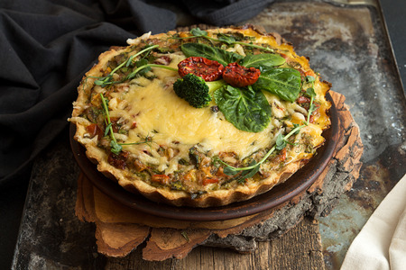 French opened pie quiche with tuna  chicken, broccoli, spinach, pepper, eggs, cheese and dried tomato on rustic background. Reklamní fotografie