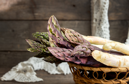 Set of raw white, green, purple asparagus on old wooden rustic  background. Copy space.