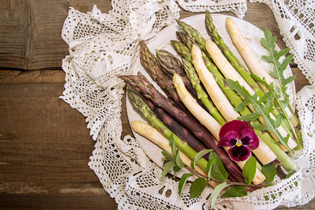 Set of raw white, green, purple asparagus on old wooden rustic  background: white, green; purple asparagus. Overhead. Top view. Copy space.