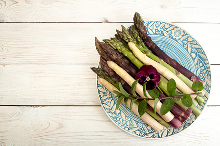 Set of raw white, green, purple asparagus on white wooden background. Overhead. Copy space.
