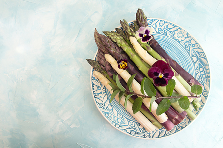 Set of raw white, green, purple asparagus on blue background. Overhead. Copy space.