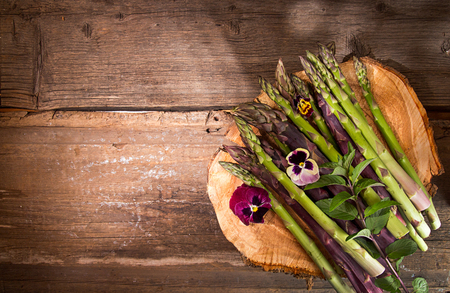 Set of raw white, green, purple asparagus on old wooden rustic  background. Overhead. Copy space.