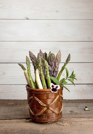 Set of raw white, green, purple asparagus in flowerpot with violet and mint. Organic healthy eating concept. Copy space.