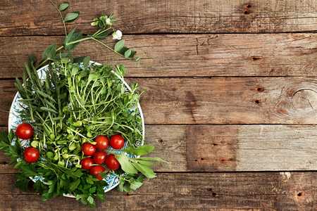 Ingredients for preparing summer salad. Cherry tomato, greenery,  arugula, parsley, sprouts, branch blossom pea on white blue plate over on old wooden rustic background. Flat lay. Overhead. Copy space