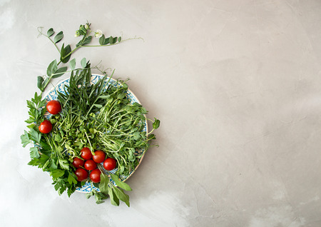 Ingredients for preparing summer salad. Cherry tomato, greenery,  arugula, parsley, sprouts, branch blossom pea on white blue plate over on gray concrete background. Flat lay. Overhead. Copy space.