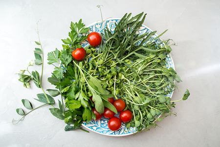 Ingredients for preparing summer salad. Cherry tomato, greenery,  arugula, parsley, sprouts, branch blossom pea on white blue plate over on gray concrete background. Flat lay. Overhead.