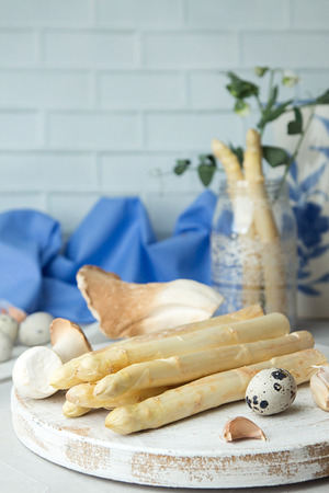 Still life with organic white asparagus, oyster mushrooms, garlic and quail eggs against white brick wall background. Healthy dieting food concept.