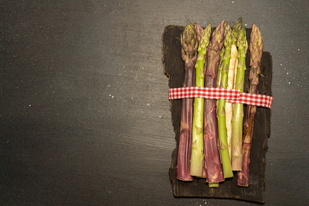 Purple green white asparagus flat lay on black stone background. Vegetarian dieting organic healthy eating concept. Copy space. Stok Fotoğraf
