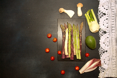 Ingredients for preparing healthy meal. Cherry tomato, asparagus, cherry tomatoes, chicory, fennel, avocado, oyster mushrooms over on black background. Flat lay. Overhead. Copy space.