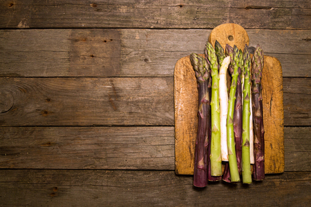 Set collection purple green white asparagus flat lay on old wooden rustic background. Vegetarian dieting organic healthy eating concept. Copy space. Flat lay. Overhead.