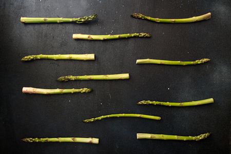 Background flat lay green asparagus on black table.