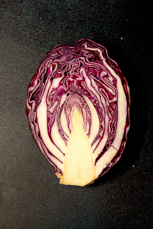 Red cabbage on black background. Half cut cabbage.