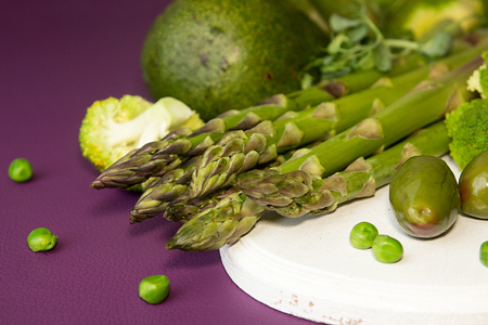 Green asparagus on white cutting board over on purple surface. Healthy eating.