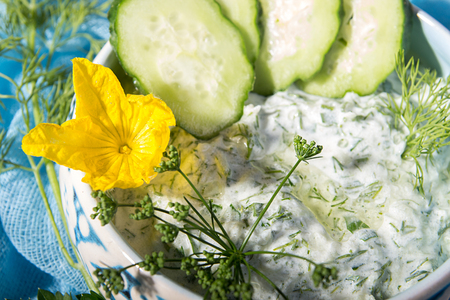 Dip sauce appetizer tzatziki of cucumber, yogurt, garlic, lemon and dill. Creece cuisine. Blue wooden background. Close up.